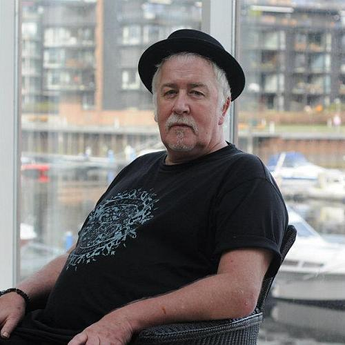 Ein Mann mit Hut sitzt entspannt in einem Sessel