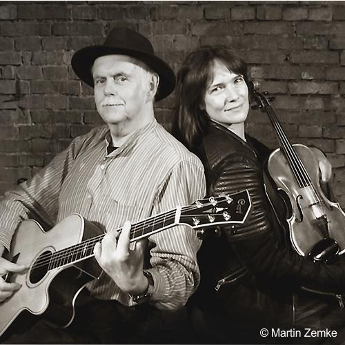Eine Frau mit Geige und ein Mann mit Gitarre